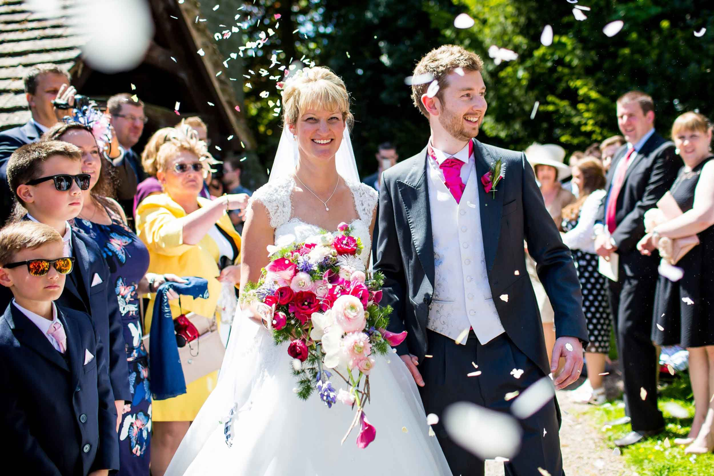 Happy couple at their church wedding, Bride'shower bouquet, button hole, confetti, Contemporary Flowers.