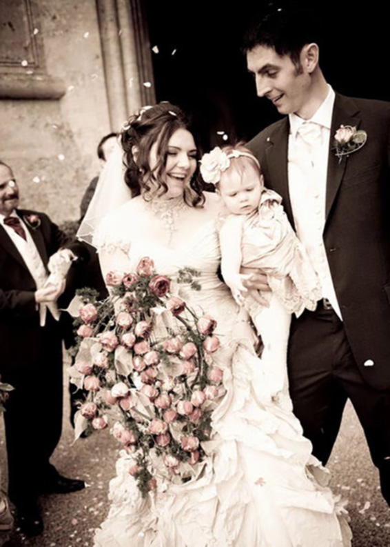 Belvoir Castle entrance, Happy couple holding their baby, confetti and flowers