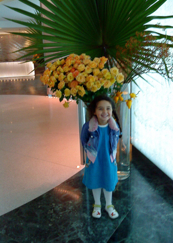 Little girl in front of yellow roses and fan palm vase hotel contract