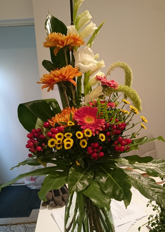 Contract tall line arrangement in vase with gerbera,gladioli and tropical leaves