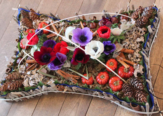 Natural garden pillow tribute with anemones, conkers, skeletal leaves and pine cones
