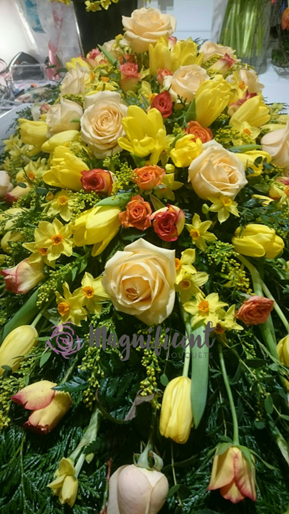 Large Coffin spray, yellow spring flowers, roses, tulips, daffodils, solidaster.