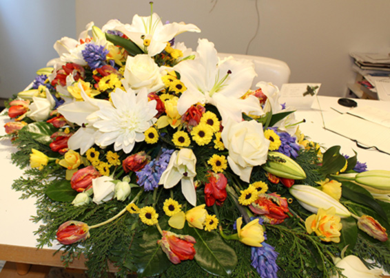 Colourful coffin spray, water lilies, roses, daffodils, tulips, hyacinths, chrysanthemums