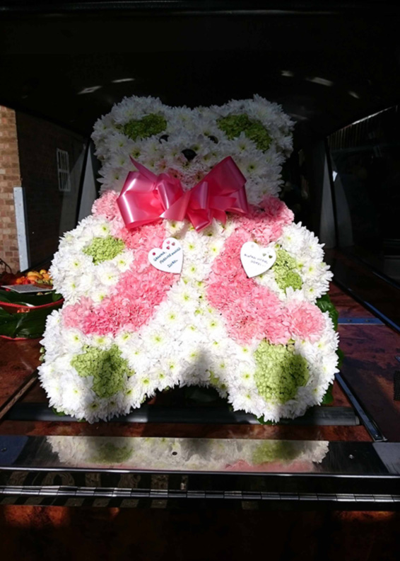 Large pink teddy bear tribute on a casket