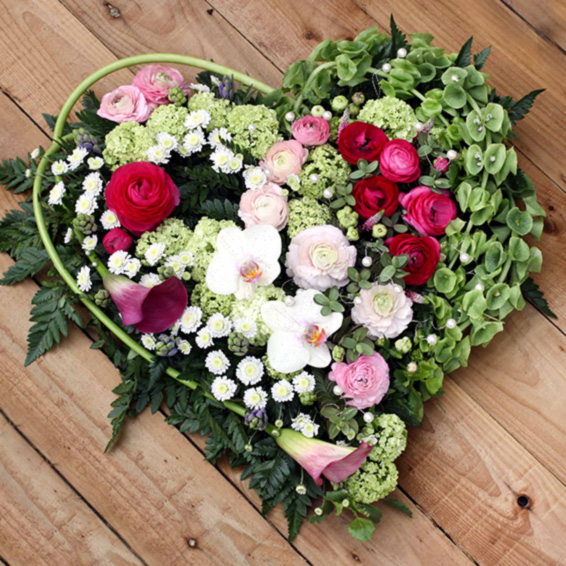 Orchids, ranunculus, stallions, calla lilies in a heart shaped funeralTribute