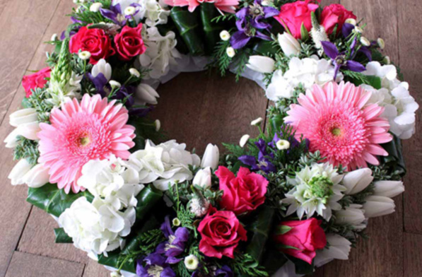 Pink gerbera, hydrangea, roses and clematis funeral wreath