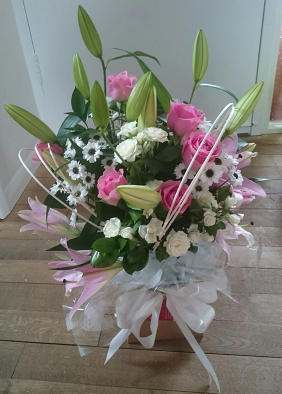 Pink roses, white lilies, spray chrysanthemums, caged, Seasonal bouquet