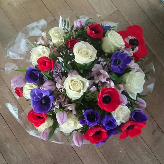 White avalanche roses, red and blue anemones, lilac tulips, handtied bouquet