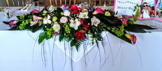 Top table wedding flowers, orchids, calla lilies, ranunculus, bear grass, pearls